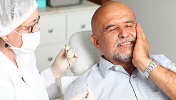Older man in dental chair holding jaw