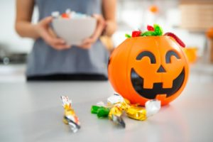 A jack-o-lantern bucket filled with candy.